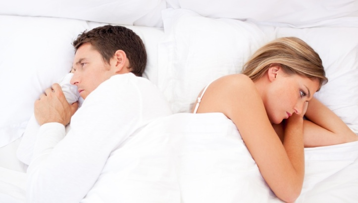 Sad couple having an argument lying on bed