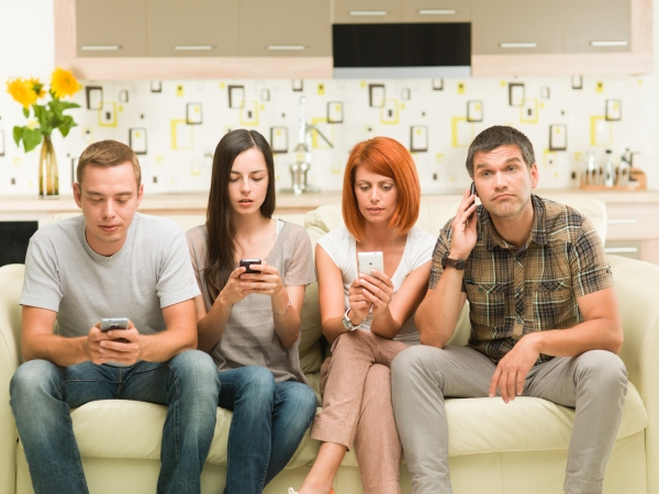 friends sitting on sofa and playing on their phones